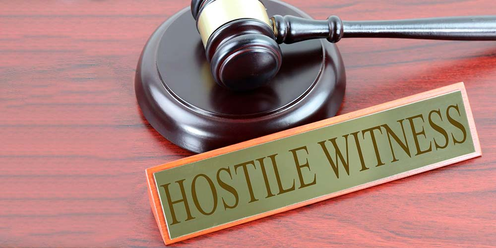 A highway sign reading 'hostile witness' illustrates the concept of difficult witnesses in a deposition.