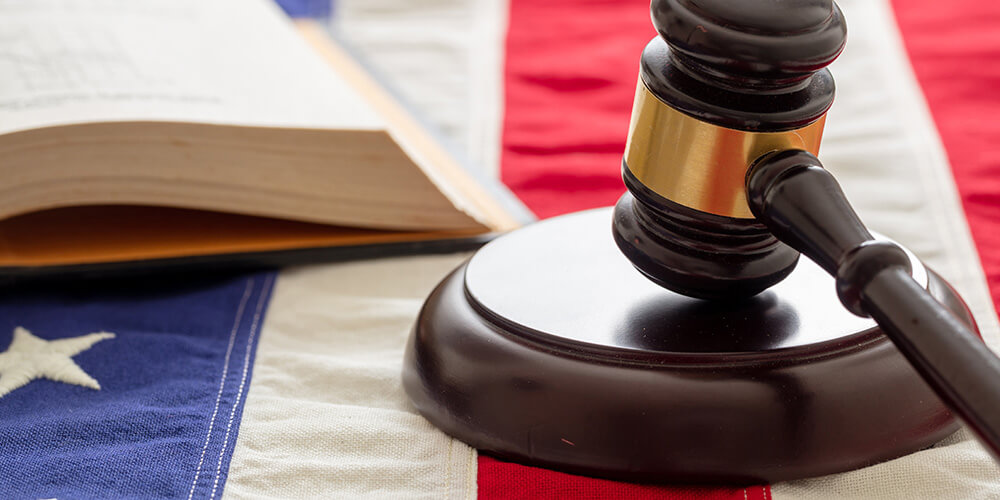 The image of a legal book and gavel resting on the American flag evokes the concept of privilege objections in a deposition.