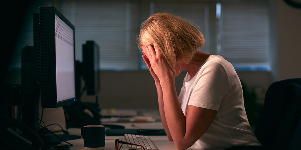 A woman sits at her desk with her head in her hands due to her fear of remote depositions.