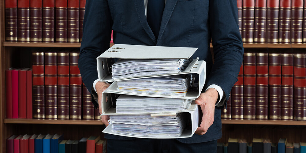 Photo depicting an attorney holding deposition notes and standing in front of shelves of legal books.