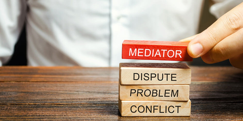 Concept art depicting the arbitration process using toy blocks, which have been labeled with the words mediator, dispute, problem and conflict.