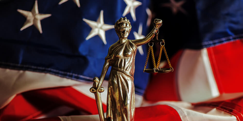 Concept art showing Lady Justice against a background of the American flag