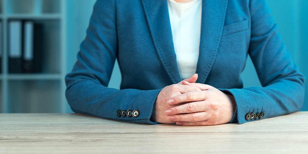A professionally dressed female attorney displays good posture, which is an important part of deposition body language.