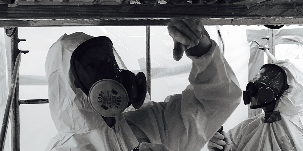 Black and white photo of a technician in a hazmat suit treating asbestos, which will lead to a remote asbestos jury trial.