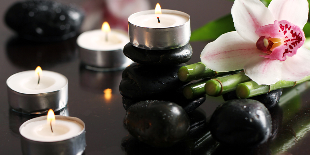 Photo of hot rocks and traditional spa decor, illustrating the topic of self-care and wellness for court reporters.